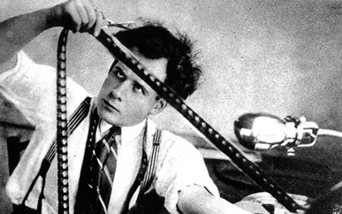 Old black and white photo of a man editing a strip of film with a pair of scissors.