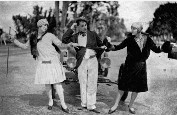 Emerson Romero performing in a silent film as Tommy Albert with two female actors in front of a vintage car.
