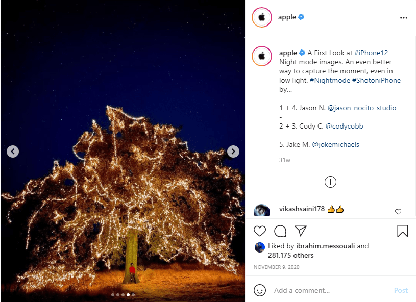 Instagram post of man standing under tree with fairy lights at night
